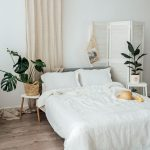 White Bedding Treatment White Top Bedside Tables Houseplants On Woven Planter Light Wood Floors Dramatic Dusty White Wall Draperies
