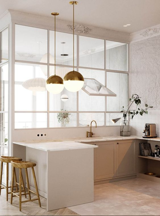 white kitchen counter with white countertop white cabinets huge pendants with brass accents small kitchen bar with wood stools semi blurr glass panel as the room divider