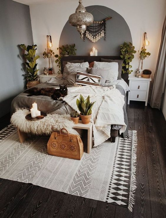 Boho area rug with tassels bedding linen in layers wood bench bed with shag cushion some potted greenery macrame wall decor Moroccan pendant white finish wood nightstand
