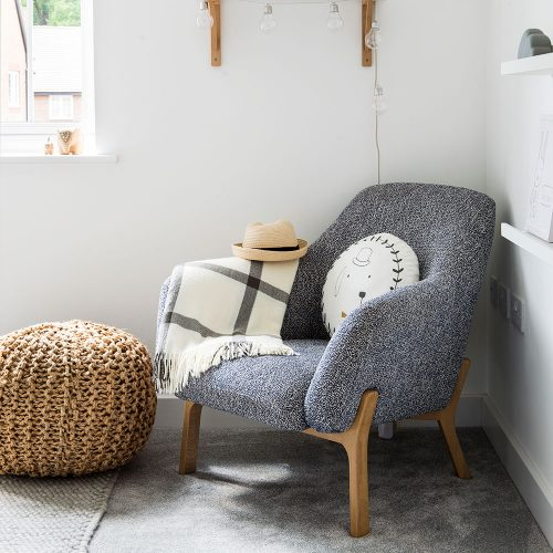 armchair in textured gray upholstery and wood frame knitted pouffe