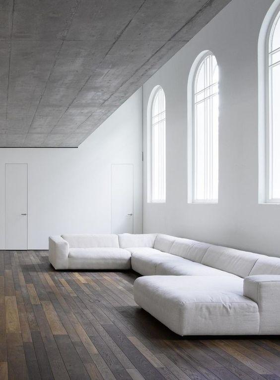 beton ceilings purely white walls modern white modular sofa wood plank floors