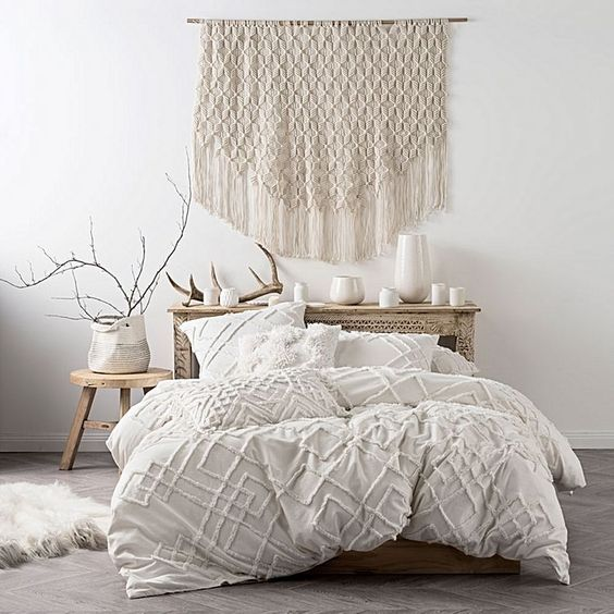 bright and airy contemporary Boho bedroom with white textured quilt cover wood bedroom furniture set and a big macrame wall decor