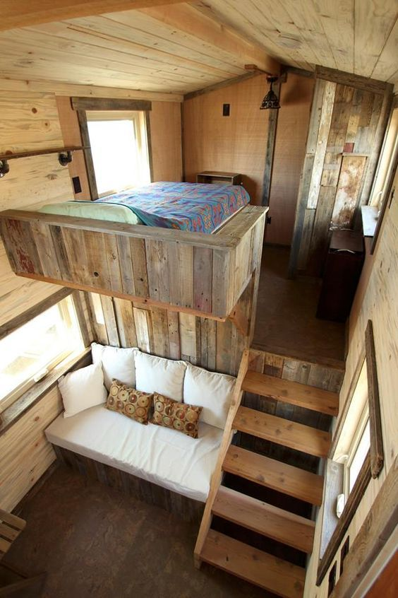 cabin's interior with bed on top wood staircase white sofa
