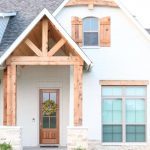 Farmhouse Exterior With Natural Wood Finishes In Several Spots