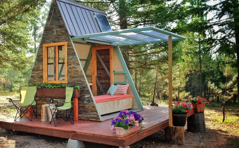 guest cabin with opened slanted panel with bed frame a couple of director chairs tree trunk side table
