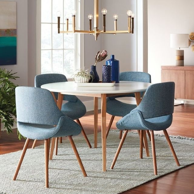midcentury modern upholstered dining chairs in blue round shaped dining table in white with wooden legs flat woven area rug fancy modern chandelier