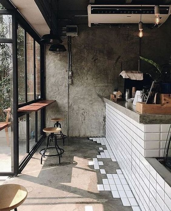 modern industrial interior rough concrete walls glass windows and door with black frames and trims wood table with indusrial stools