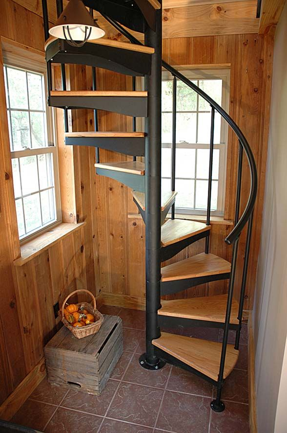 rustic style spiral staircase with natural wood steps and heavy metal railings in black
