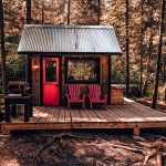 Small Cabin With Red Front Door And Chairs