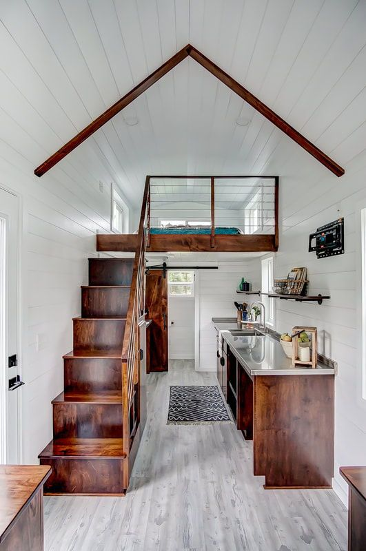 tiny house design dark finished wood staircase railings kitchen counter and beams purely white ceilings and walls whitewashed wood floors