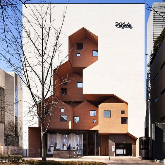 ultra modern exterior facade consisting of purely white concrete finish highlighted with earthy tanned building stories