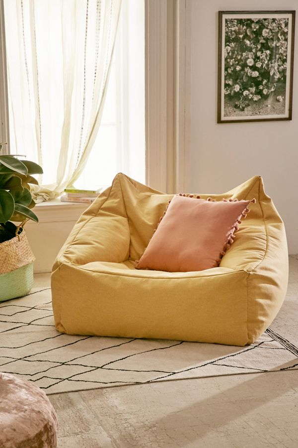 vivid yellow bean bag with soft pink accent pillow modern area rug in white with black accent lining motifs