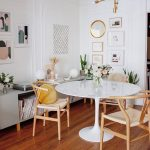 Boho Minimalist Dining Room With Round Shaped Marble Like Dining Table Light Wood Dining Chairs In Modern Style Wood Floors