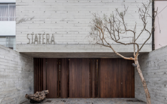 Statera restaurant exterior exposing concrete walls and floors wood exterior door dramatic tree
