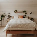 Airy Boho Style Bedroom With Wood Bed Frame White Wood Plank Walls Light Wood Floors Some Greenery On Pots