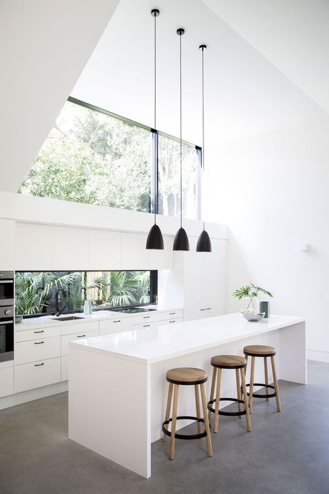 all white kitchen and breakfast nook wood stools with round tops black pendants concrete floors