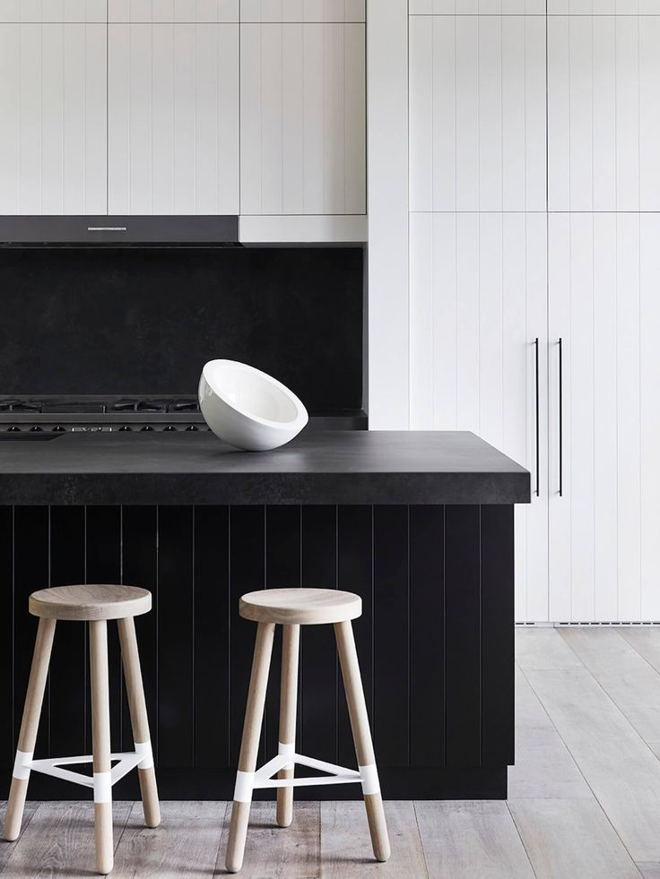 black kitchen island with ornate white sink ultra light wood stools black wall accent