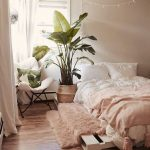 Bright And Airy Bedroom With Ultra Soft Pink Blanket White Bed Linen Ultra Soft Shag Rug Platform Bed Frame Corner Chair With White Cushion Tropical Houseplant On Woven Planter
