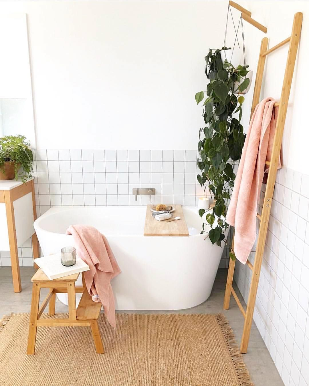 bright and light bathroom white bathtub wood ladder rack vivid vines white ceramic tile walls flat woven runner with fringed tassels wood stool