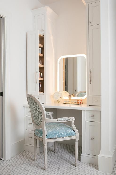 built in vanity in white with drawer system and mirror chair with light blue cushion