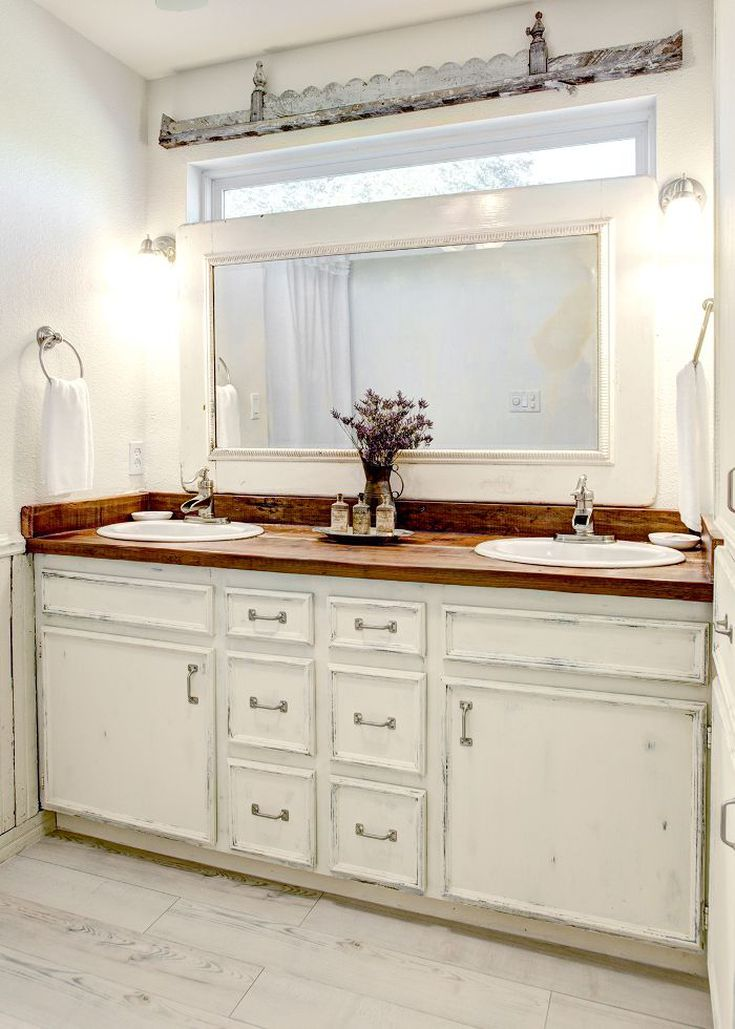 country inspired bathroom vanity with wood top white framed mirror a couple of white sinks and white cabinets
