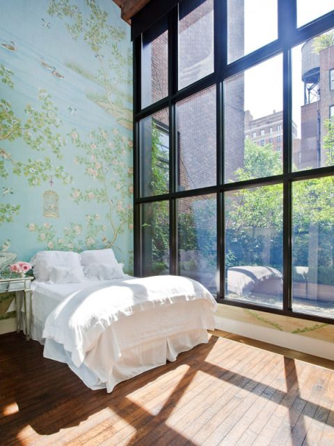 farmhouse style bedding idea in white wood plank floors full height glass window with black metal frame and trims floral wallpaper