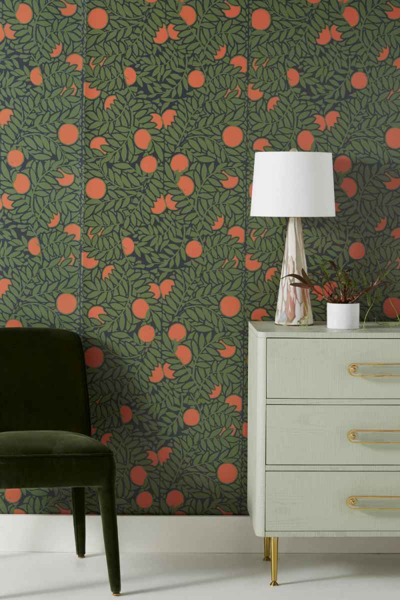 floral wallpaper in green and orange white dresser with gold toned handles and legs dark green velvet chair