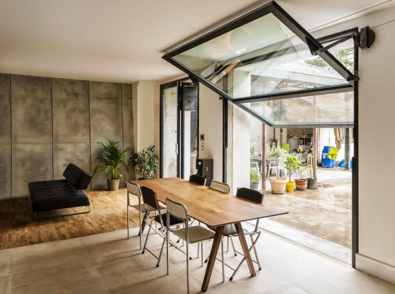 garage conversion into a cool loft with glass garage door modern black sectional wood dining table modern black dining chairs