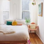 Light And Airy Bedroom With White Bedding Linen Colorful Throw Pillows Midcentury Modern Corner Chair In Orange Wood Plank Floors