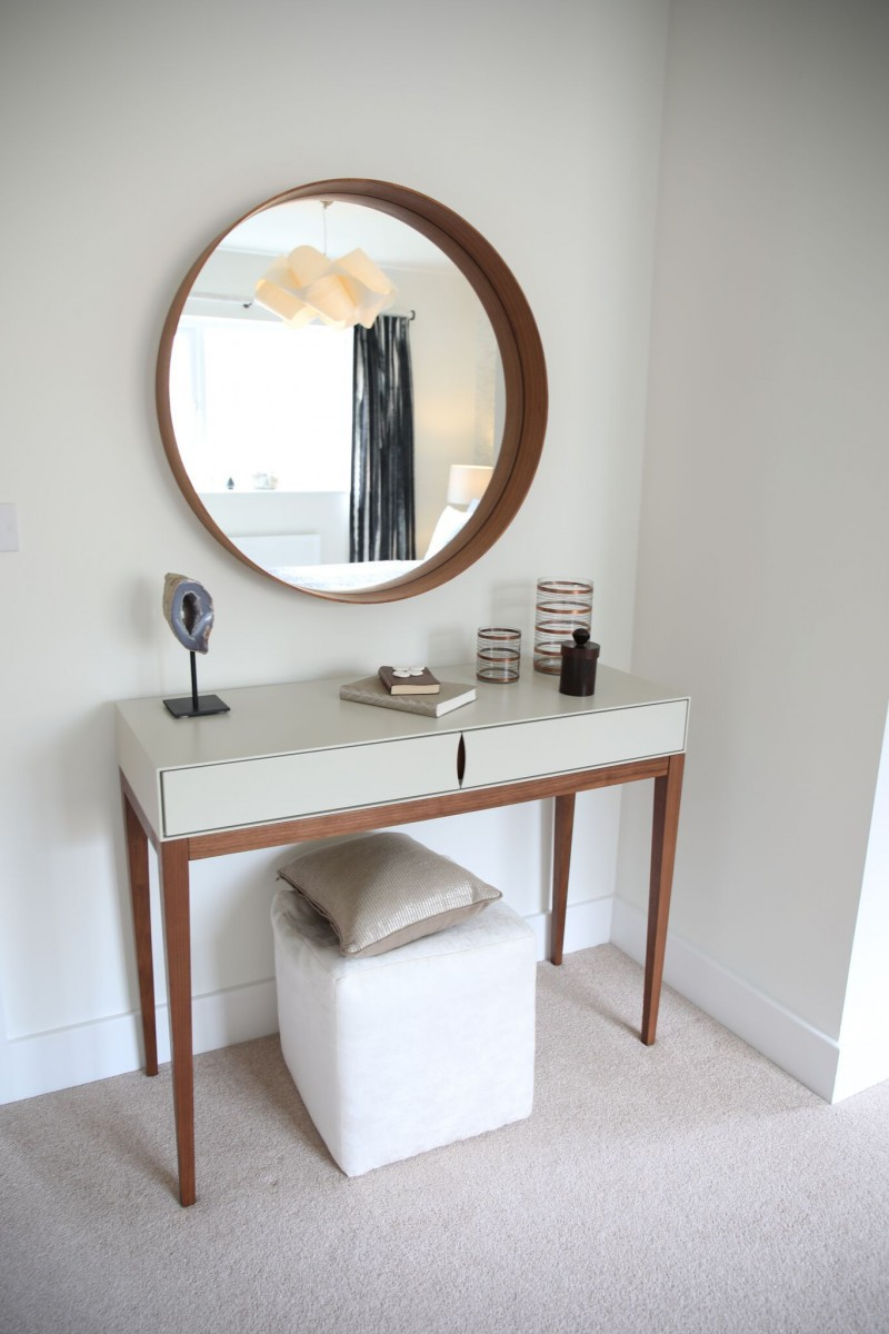 light and airy dressing area with white top dressing table white stool wood framed round mirror