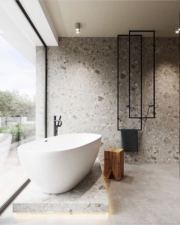 master bathroom design with textured walls modern white bathtub wood stool concrete tile floors black piping installation