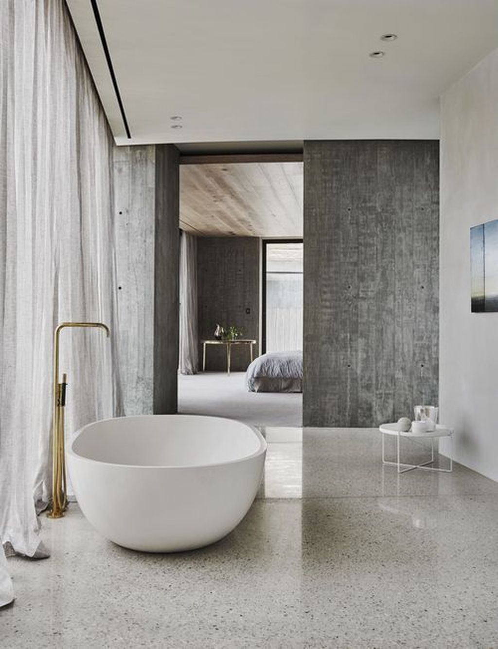 minimalist master bathroom with brass stand faucet modern white tub beton walls dramatic gray drapery