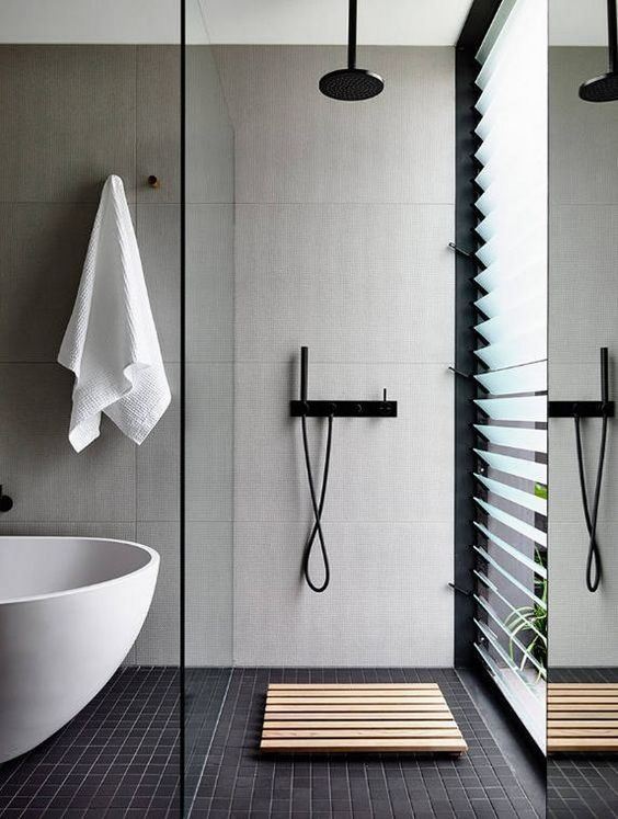 minimalist style bathroom in black white walk in shower with black tile floors and light tile walls wood mat for shower area glass room partition white tub