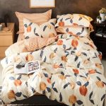 Peach Comforter Black Rug With Gray Line Accents Wood Bedside Table