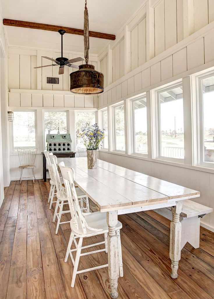 rustic modern dining room with white dining chairs white dining table dark toned  pendant dark ceiling fan  on exposed wood beam wood floors series of glass windows