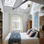 Simple Minimalist Bedroom Idea White Bedding Linen Colorful Pillows Blue Throw Blanket Glass Skylights Exposed Wood Beam In Black Oversized Bulb Pendant