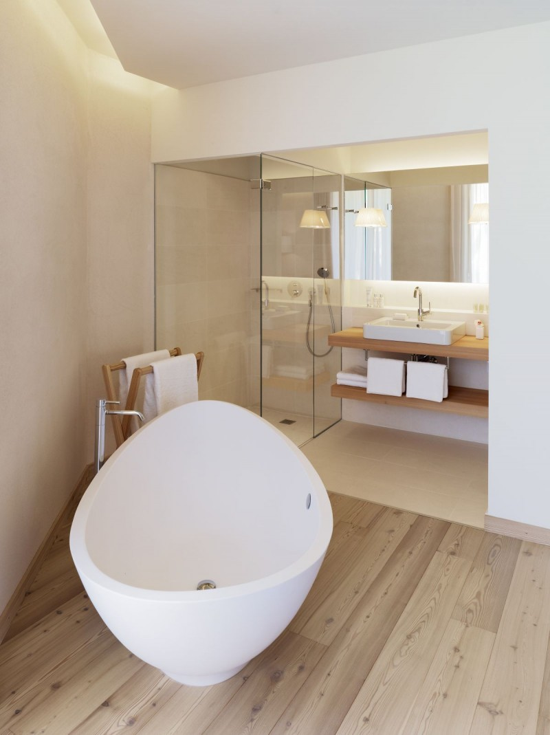 warm minimalist master bathroom idea modern white bathtub wooden towel hanger wooden bathroom vanity with white sink and under shelving unit walk in shower with glass room partition