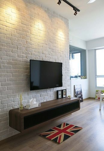 white brick wall wall mounted TV dark wood media console table British flag mat light wood floors