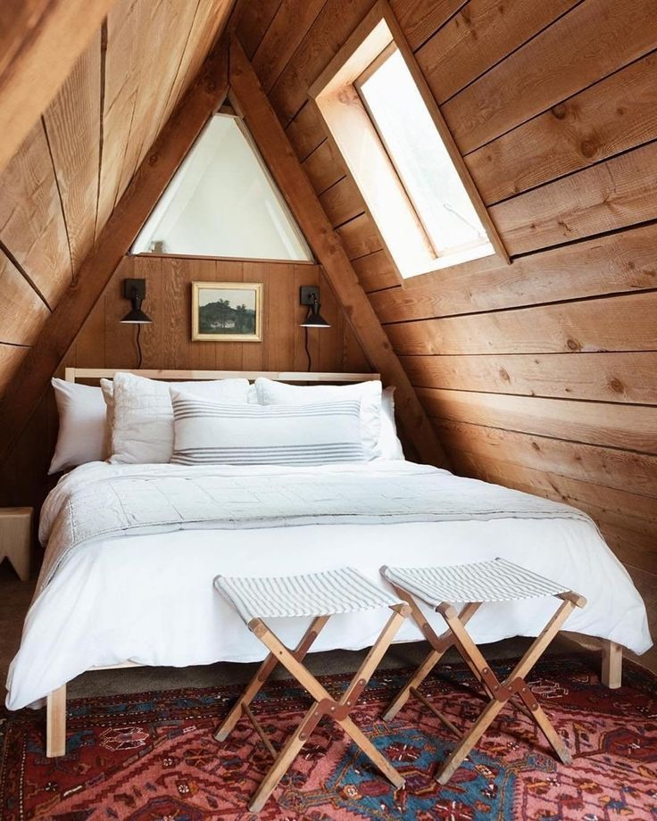 wood bed frame with headboard white bedding treatment x base chairs multicolored area rug wood plank ceilings with skylights