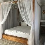 Wood Canopy Bed With Semi Transparent Draperies In White White Bedding Linen