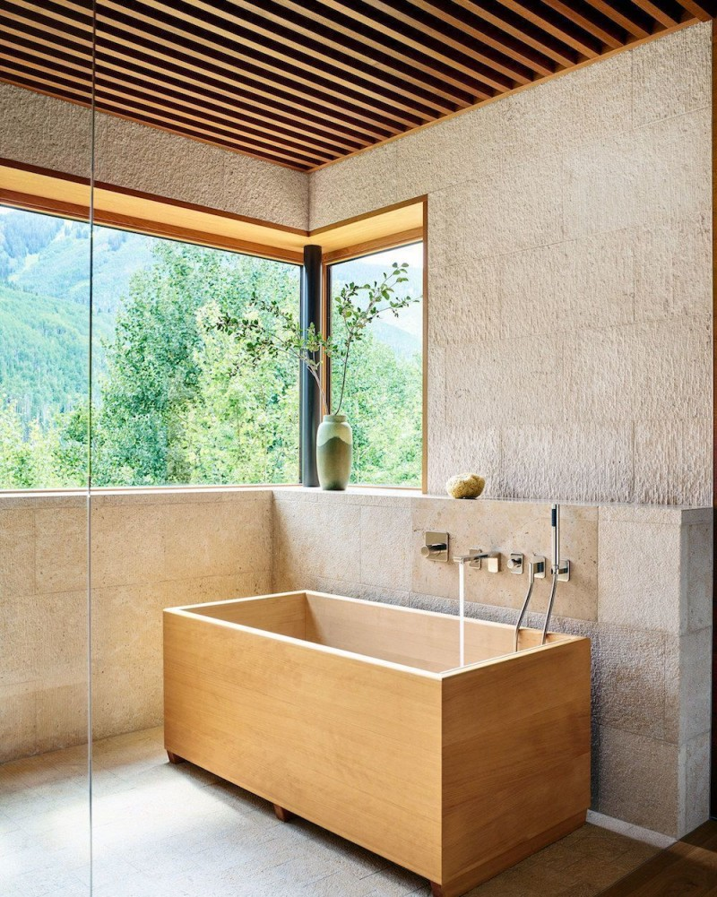zen feel modern master bathroom design with rectangular shaped wood bathtub hard texture concrete walls frameless glass windows