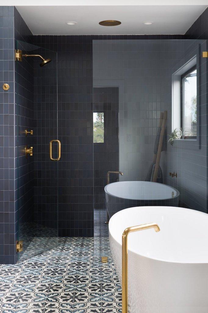 black tiled walls vintage tile floors white bathtub brass shower faucet clear glass shower room partition