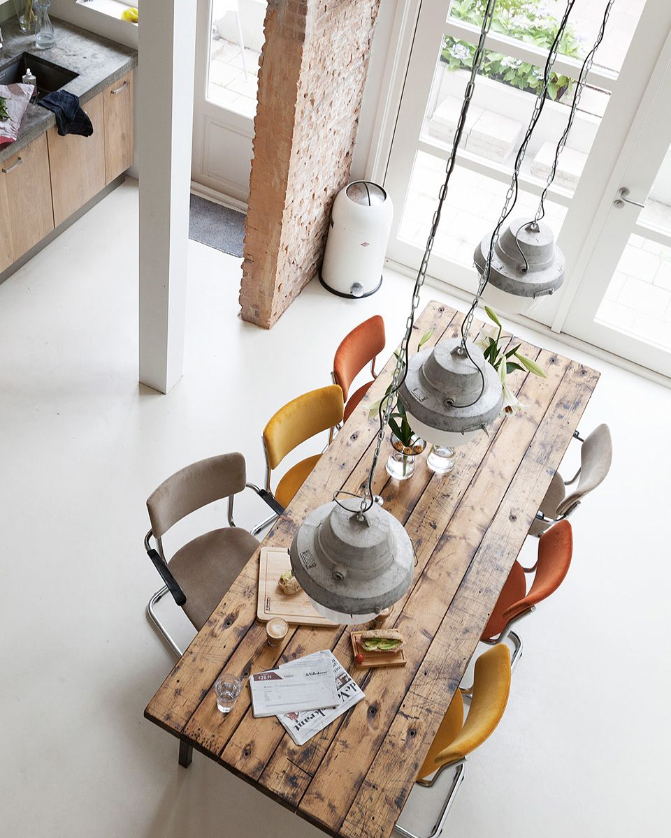 clean industrial dining space with wood plank dining table colored dining chairs industrial pendants