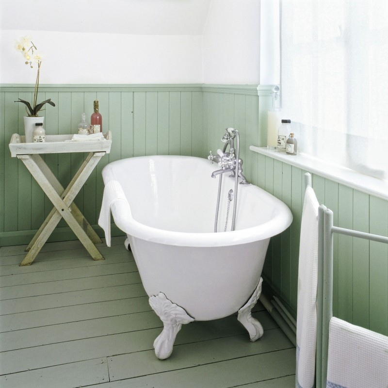 light green baseboard white walls claw foot bathtub in white x base side table