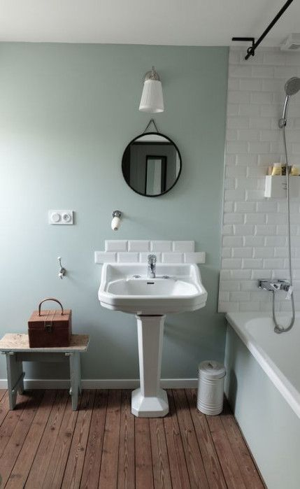 light green bathroom wall featuring white brick wall wood plank floors free standing bathroom vanity in white with white tile backsplash
