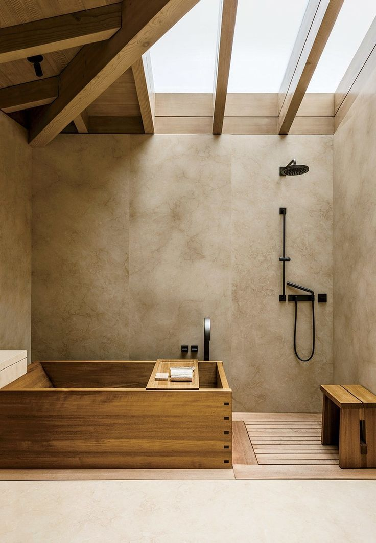 light toned concrete walls black metal shower hardware wooden Japan tub wooden bench seat for shower