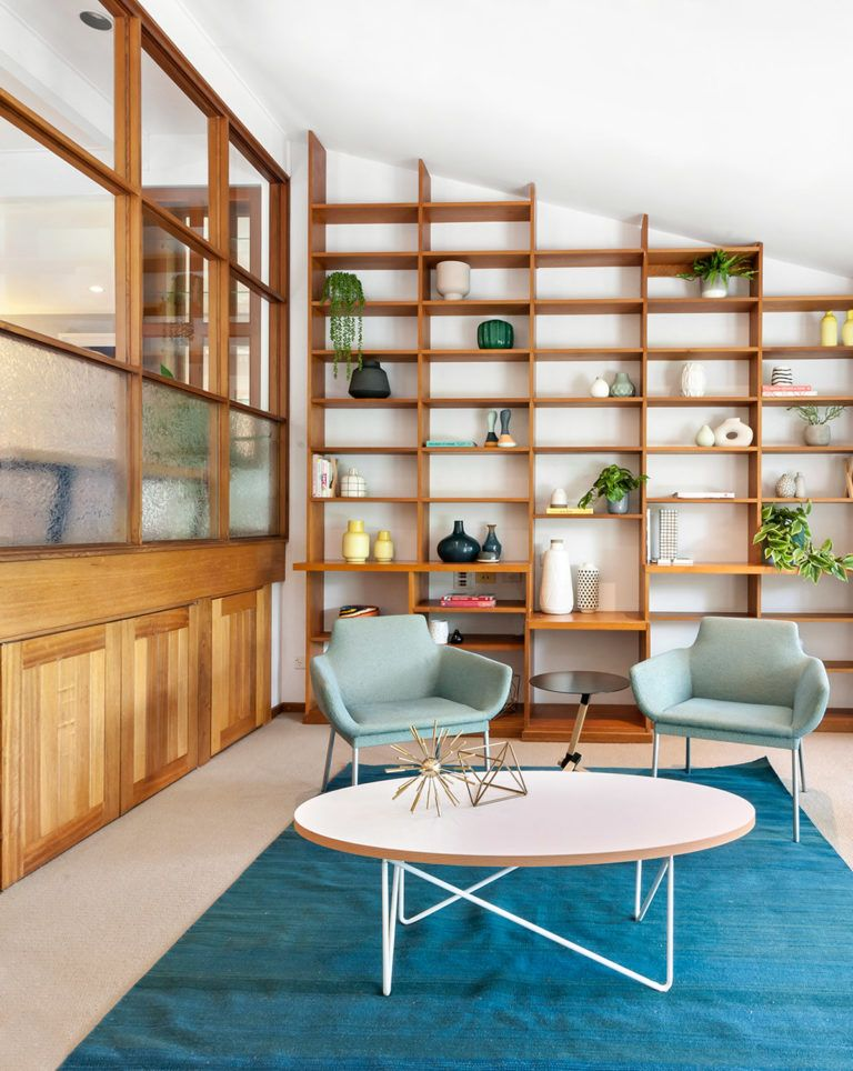 midcentury modern living room with huge wooden display rack fabulous chairs in light blue oval shaped coffee table blue area rug wood space divider with blurred glass addition