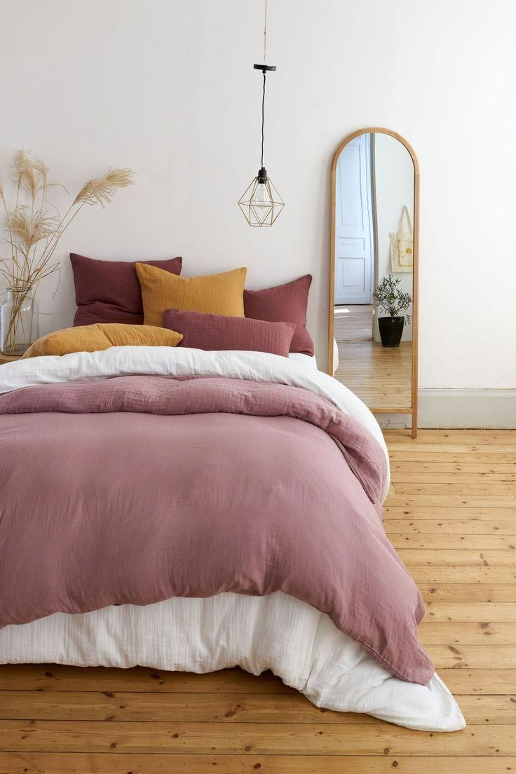 minimalist bedroom idea with white deep pink duvet cover wooden plank floors wood framed standing mirror