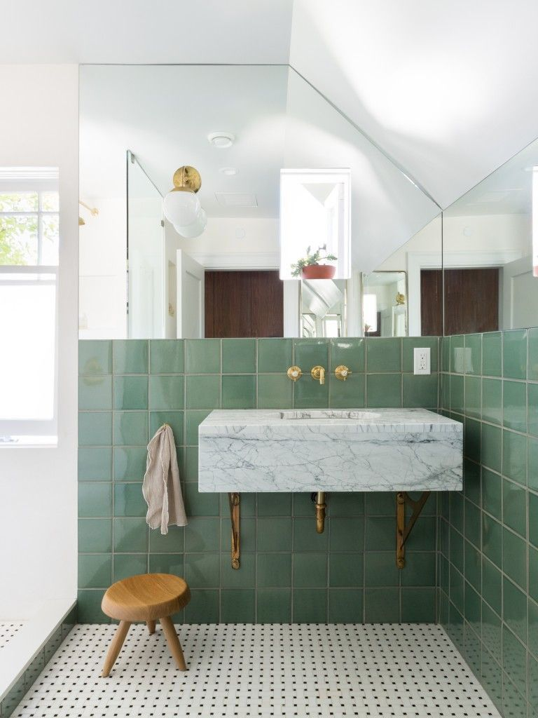 modern bathroom design with green tile walls white mosaic tile floors marble bathroom vanity with brass faucet small wooden stool frameless mirror