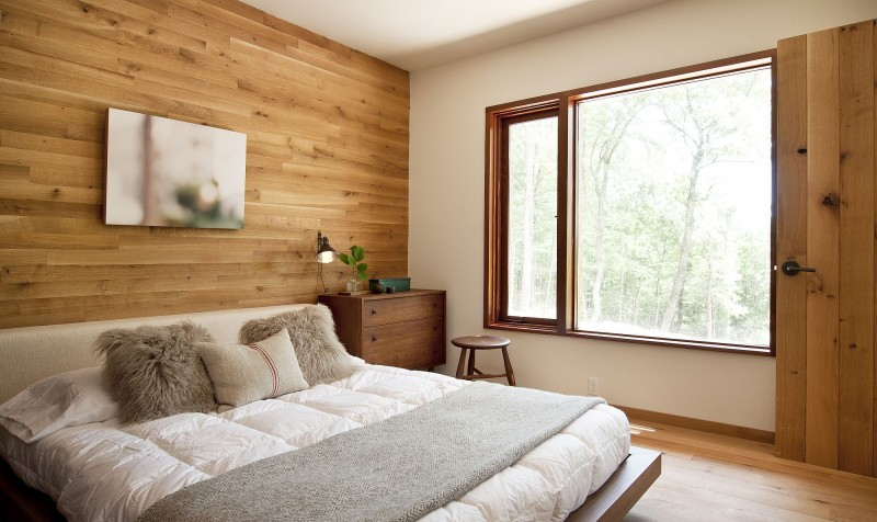 modern bedroom with white bedding set wood walls wooden nighstand wood stool glass windows with wood frames wood floors
